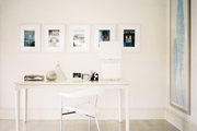 A framed photography series above a white desk and a contemporary office chair