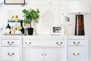 A white sideboard decorated with art and a tray of bar essentials