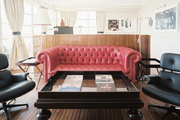 A red tufted couch and a pair of black chairs in a sitting area