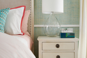 Glass lamp atop nightstand with drawers.