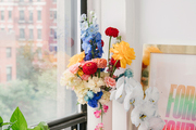 A colorful floral arrangement and a gold picture frame sitting next to a bedroom window.