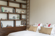 A bedroom with white bedding and a convenient ladder to reach the top of the bookshelf.