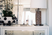A leopard-print lamp on a mirrored chest of drawers