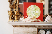 Layered art and home accessories on a marble mantel