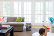 Sheepskin rugs and a natural-fiber rug in a living space with french doors