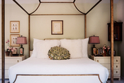A canopy bed with white linens