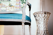 A settee with chinoiserie upholstery next to a faceted hourglass table