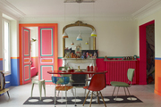 Colorfully painted double doors connect a Paris apartment's dining room to a bedroom beyond