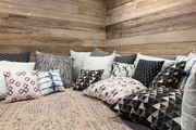 Natural wood walls surrounding pile of patterned throw pillows.