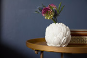 An artichoke-shaped candleholder diguised as a vase on a nightstand