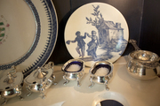 A collection of silver serving pieces and blue-and-white tableware