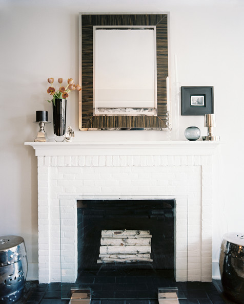 Log On - A neat stack of birch logs make this white brick fireplace a focal point even when it