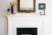 Logs in a white-painted brick fireplace