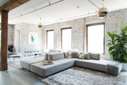 Large window lit living space with brick walls and gray sectional.