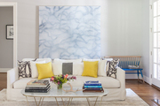 Large scale art behind modern furniture in grey living room.