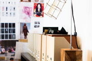 File-box organizers atop a wooden shelf lit by an industrial-inspired lamp