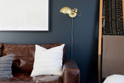 A brown leather sofa in a contemporary living space with navy blue walls.