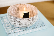 Round Candle Holder atop small table.