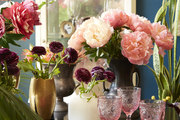 A variety of floral arrangements sitting on a dining room table.