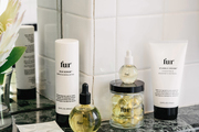 Lotions and toiletries sit on a marble bathroom counter top.