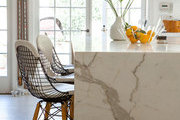 A Calacatta Gold marble kitchen island with Modernica bar chairs