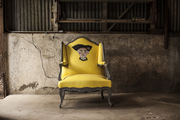 A whimsical yellow chair in a rustic barn