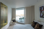 The guest room, with a view of the Thames, in the home of London designer Tara Bernerd