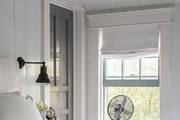 An armed wall sconce and vintage fan beside a bed in a master bedroom