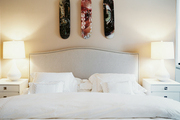 Marilyn Minter skateboard art in a neutral bedroom with a pair of white lamps