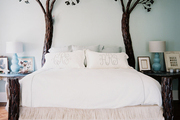 A handcrafted iron bed frame paired with neutral bedding