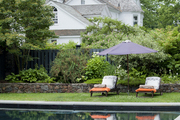 Chaise lounges and an umbrella beside a built-in pool