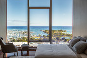 A contemporary gray and neutral bedroom with a view of Honolulu.
