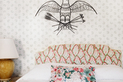 An upholstered headboard and a floral pillow in a wallpapered bedroom