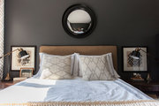 A bed with white linens and sweater knit pillows, framed by brass library lamps