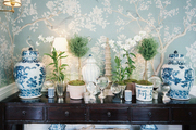 Potted plants and blue-and-white ginger jars on a wooden sideboard