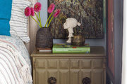 A bedside table topped with eclectic objects and surrounded by vintage artwork