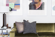 A green velvet sofa sits beneath a series of bright portraits