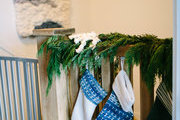 A detail of indigo stockings and a garland on a railing.