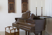 Antique wooden panels and piano in living room.