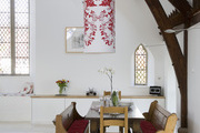 A dining space in a converted church with stained glass, church pews, and a large cylinder statement light fixture.
