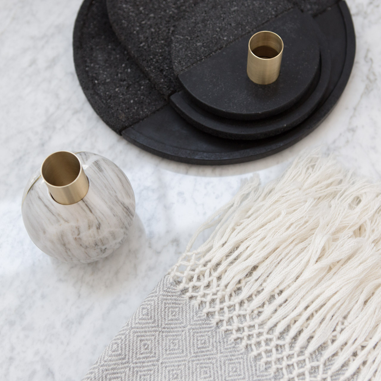 Lava trays and marble candle holders add an earthy element to a minimalist vignette.