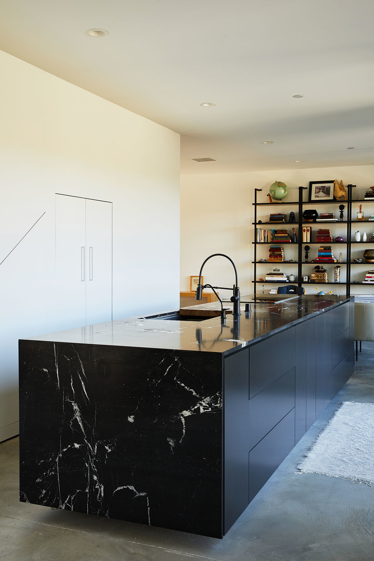 A custom marble kitchen island anchors the lower living level, complete with silent cabinetry and ample storage solutions. Dunn Edwards Paint | Custom Marquina Nero Marble Countertop | Custom Cabinetry | Brizo Faucet | Bosch Appliances | Kohler Sink | CB2 Shelving.