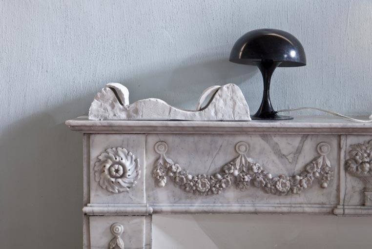 "A prototype of Marin's ""Dunes"" collection sits next to a vintage lamp on an ornate fireplace."