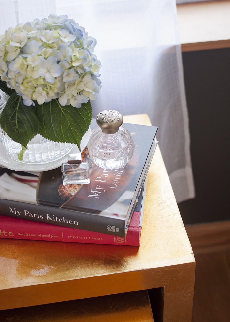 """Cookbooks and an arrangement of hydrangeas top<a  target=""""_blank"""" href=""""http://www.zgallerie.com/p-12982-astair-nesting-tables.aspx"""" target=""""_blank"""">Z Gallerie</a>&squot;s gold-leaf nesting tables."""