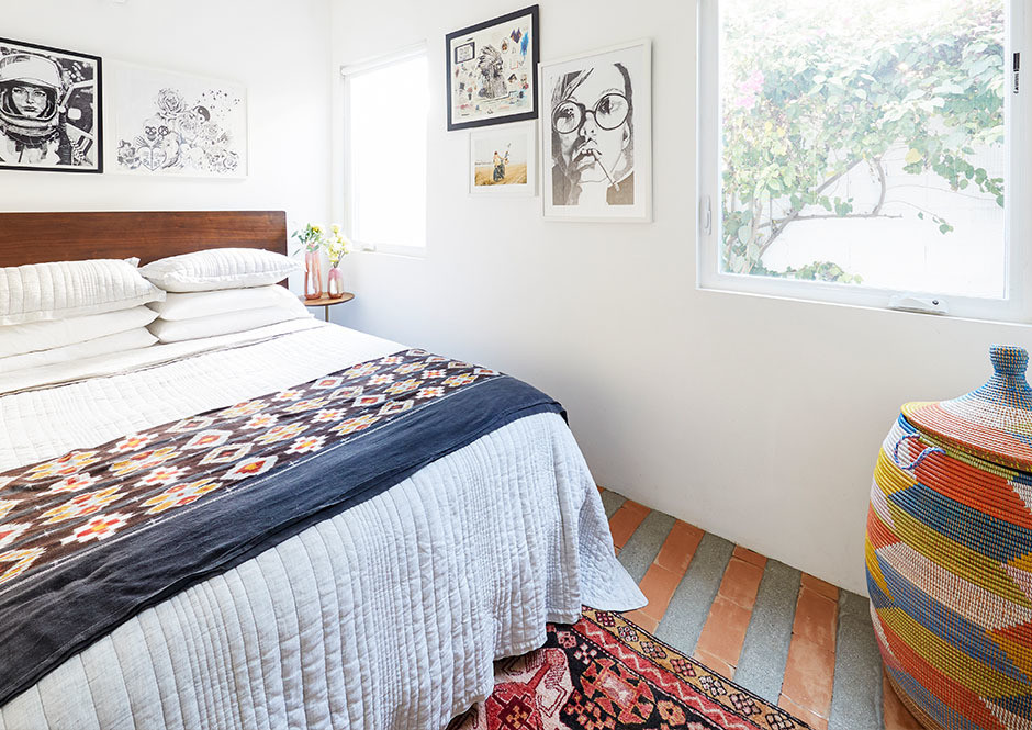 The couple's bedroom adheres to a laidback, relaxed L.A. aesthetic. West Elm Bed | Matteo Bedding | Mounser Studio Artwork | Wes Lang Artwork | Tom Bing Print | Vintage Moroccan Rug | Vintage Basket | Vintage Throw | West Elm Side Table.