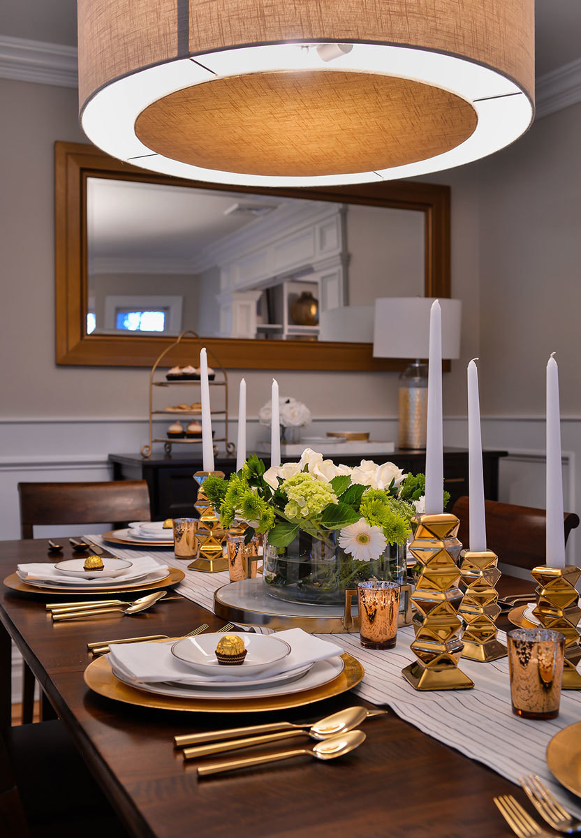 Gold flatware, chargers, and candlesticks bring a glamorous touch to the dining room's dark wood table.