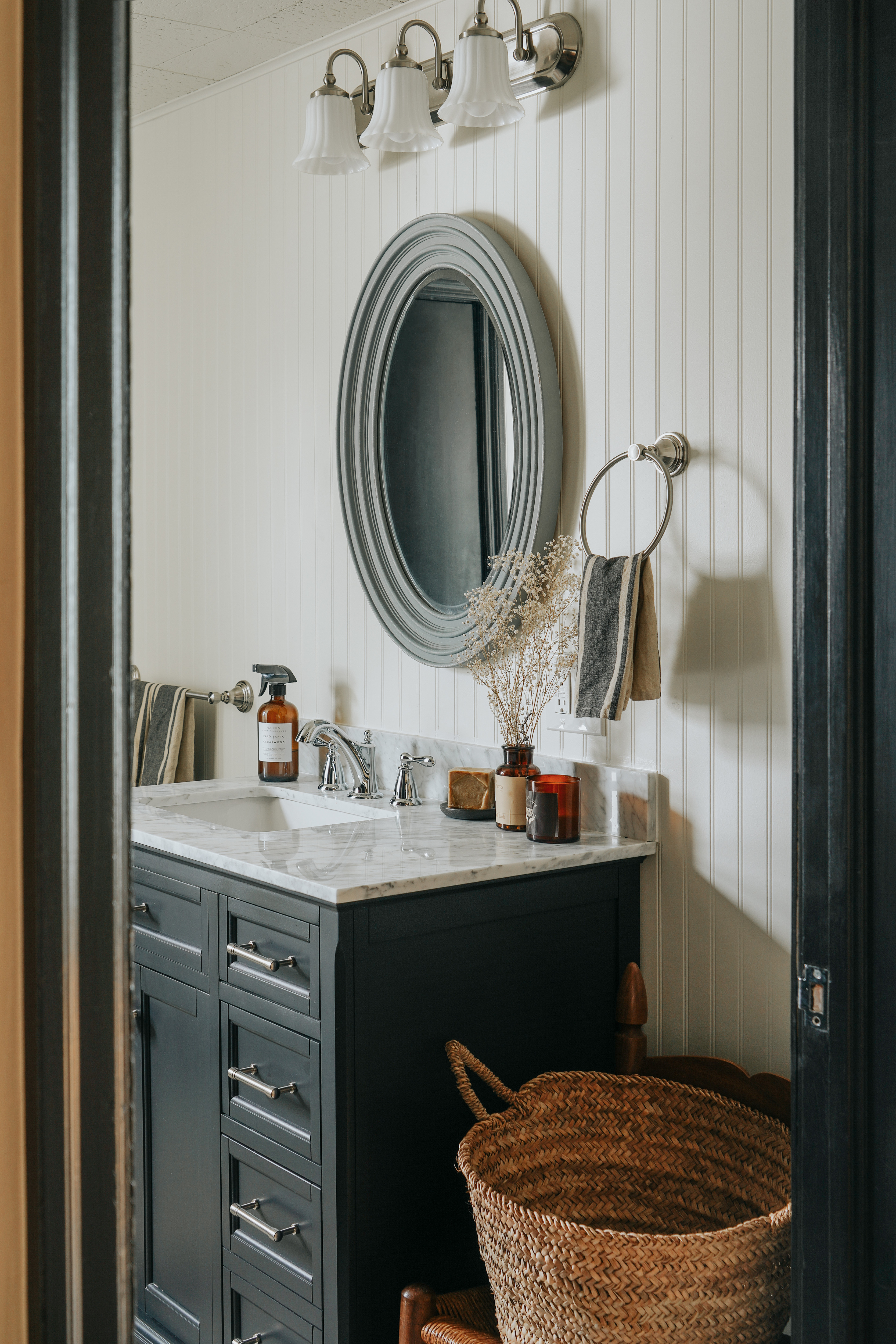 The home's historic charm even makes its way into the bathroom embracing tradition with a modern touch. Vintage basket; Vintage Mirror; Na Ni Palo Santo Room Spray; West Elm Hand Towel.