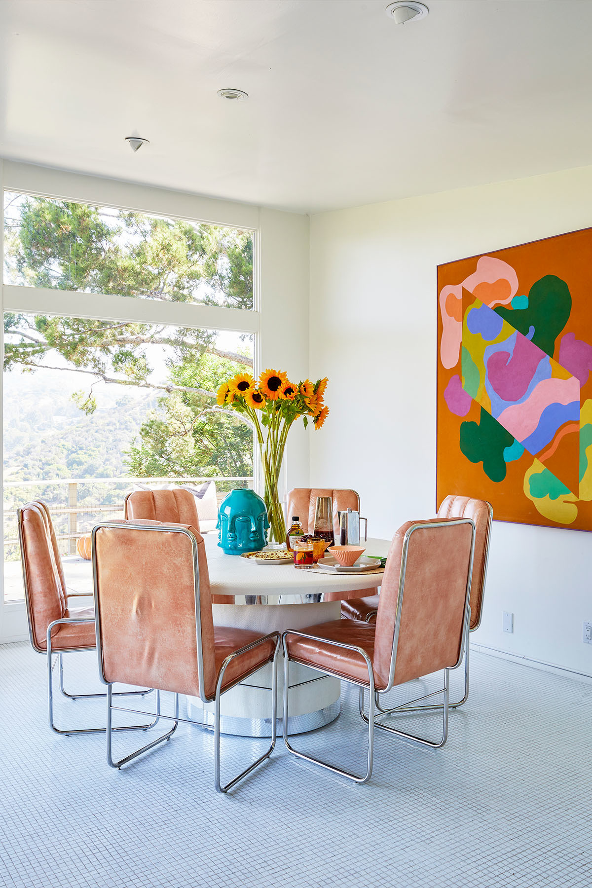 A technicolor artwork sourced via Remi Danielle Modern hovers above a Nihil Novi vintage dining table and chairs. Nihil Novi Blue Vase | CB2 Tall Vase.