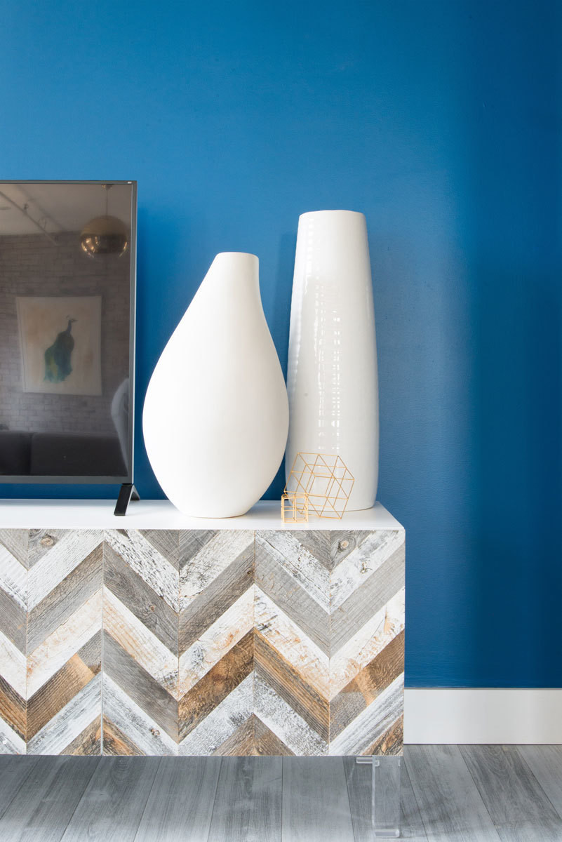 A chevron-patterned T.V. console table in reclaimed wood pops against a vibrant accent wall.