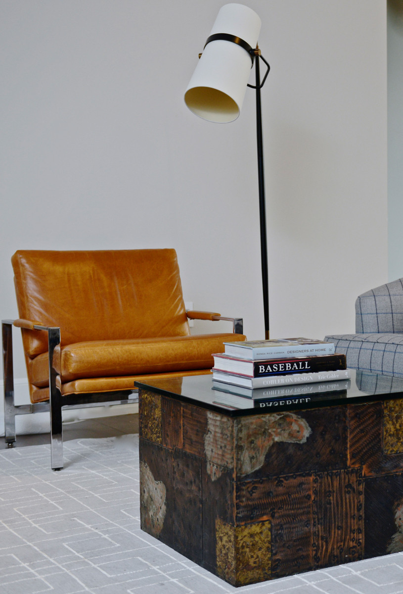 A vintage Milo Braughman chair sits next to a wood-and-glass Paul Evans coffee table.